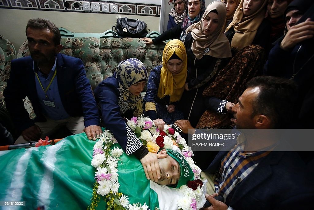 The mother (2nd-L) and father of Abdul Fatah al-Sharif, a wounded Palestinian assailant who was shot dead by an Israeli soldier after laying prone on the ground in the city of Hebron on March 24, mourn during his funeral on May 28, 2016, in the West Bank city of Hebron. An Israeli soldier caught on video shooting a wounded Palestinian assailant in the head was charged with manslaughter in a case that has sparked widespread controversy. Prosecutors presented the indictment to a military court over the March 24 killing, which occurred minutes after the Palestinian had stabbed another soldier and lay prone on the ground wounded by gunfire, according to Israeli authorities. / AFP / HAZEM