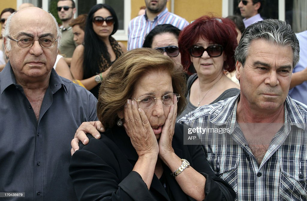 The mother (C) and father (L) of Cypriot media boss Andis Hadjicostis leave the court with their driver (R) after hearing the verdict for the murder of their son at the court in Nicosia, the capital of the eastern Mediterranean island, on June 13, 2013. Television host Elena Skordelli, a 42-year-old mother of two, her brother Tassos Krasopoulis, 37, and Andreas Gregoriou, a 33-year-old meat supplier and plumber Grigoris Xenophontos, 29, were found guilty of the contract killing and sentenced to life imprisonment. AFP PHOTO / YIANNIS KOURTOGLOU