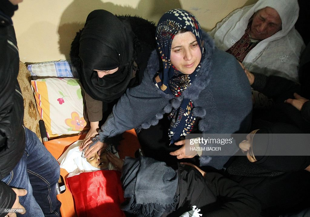 The mother (C) and relatives of Palestinian Haitham al-Bau, who was shot dead by Israeli soldiers after throwing a petrol bomb at a military jeep, mourn over his body in the village of Halhoul north of the West Bank city of Hebron, on February 6, 2016 BADER
