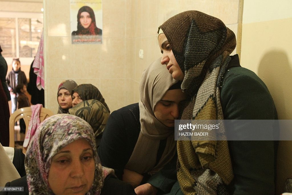 The mother (L) and sisters of Palestinian Kalzar al-Uweiwi, a Palestinian teenager who was killed a day earlier following a reported stabbing attack, mourn next to her body ahead of her funeral, in the Israeli occupied West Bank city of Hebron, February 14, 2016. Israeli forces shot dead Kalzar al-Uweiwi, 17, as she tried to stab a soldier in the city of Hebron on February 13, according to Israeli and Palestinian authorities. BADER
