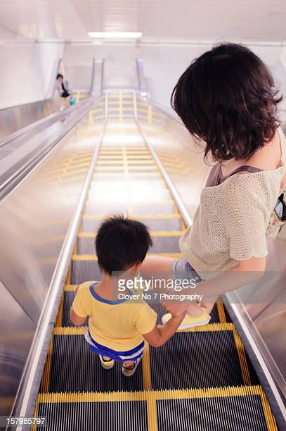 The mother and the little boy take the escalator
