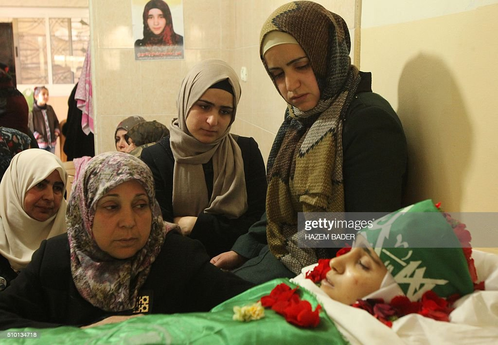 The mother (2-L) and the sisters of Palestinian Kalzar al-Uweiwi, a Palestinian teenager who was killed a day earlier following a reported stabbing attack, mourn over her body ahead of her funeral, in the Israeli occupied West Bank city of Hebron, February 14, 2016. Israeli forces shot dead Kalzar al-Uweiwi, 17, as she tried to stab a soldier in the city of Hebron on February 13, according to Israeli and Palestinian authorities. BADER