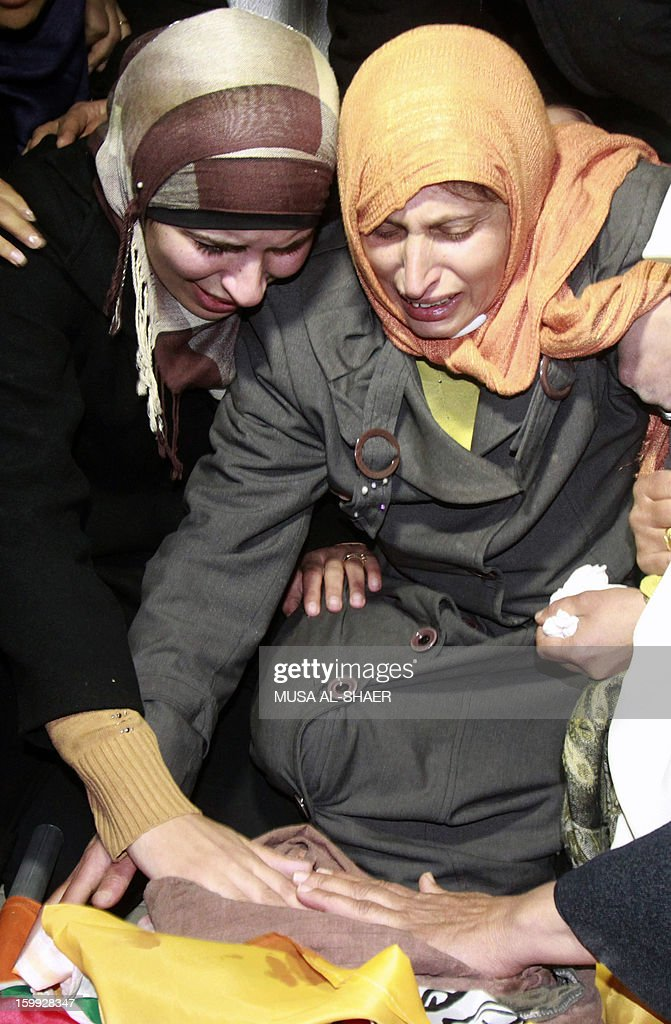 The mother of 21-year-old Palestinian Lubna Hanash mourns over her daughter's body at their family home in the the West Bank town of Bethlehem on January 23, 2013. The 21-year-old Palestinian woman died after being hit in the face by Israeli gunfire in the West Bank, medics said, with witnesses saying she was shot by soldiers. AFP PHOTO / MUSA AL-SHAER