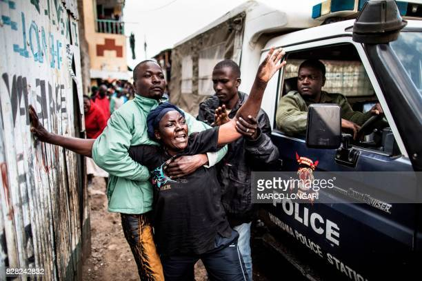 TOPSHOT The mother of a man shot in the head allegedly by Kenyan police reacts as she passes a police van transporting her son's body in an alley of...
