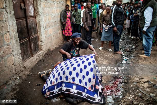 TOPSHOT The mother of a man shot in the head allegedly by Kenyan police uses a blanket to cover her son's body in an alley of Mathare slum in Nairobi...