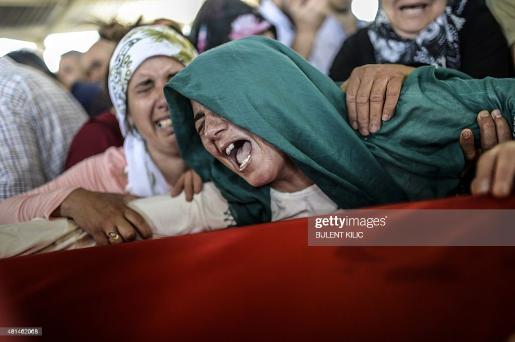 The mother of a victim cries for her son on his coffin during a funeral ceremony in Gaziantep on July 21 following a suicide bomb attack the day...