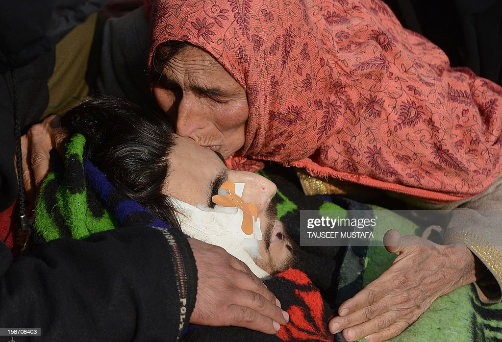 The mother of alleged Pakistan-based Lashker-e-Toiba militant Mudasir Sheikh alias Mavia a self styled 'district commander' kisses his body during the funeral of he and his Pakistani associate Tamim in Kulgam district of south Kashmir some 75kms from Srinagar on December 25, 2012. Security forces confronted the pair of rebels and in the ensuing gunbattle they and a policeman were killed. A police spokesman said that the two were implicated in an attack on The Silver Star Hotel in Srinagar and on an army convoy. AFP PHOTO/Tauseef MUSTAFA