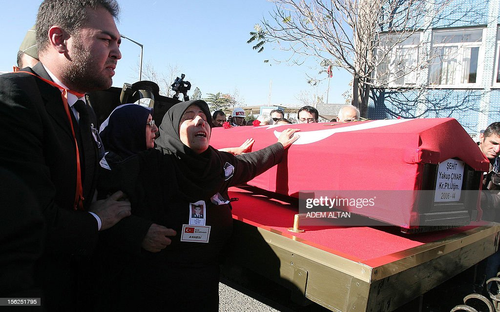 The mother of army officer Yakup Cinar, one of 17 Turkish soldiers who were killed in a helicopter crash early on November 9, 2012 in Siirt province, caresses his coffin during his funeral in Ankara on November 12, 2012. The Turkish military helicopter crashed on November 9, 2012 in bad weather in the southeastern city of Siirt, killing all 17 troops on board, local officials said.