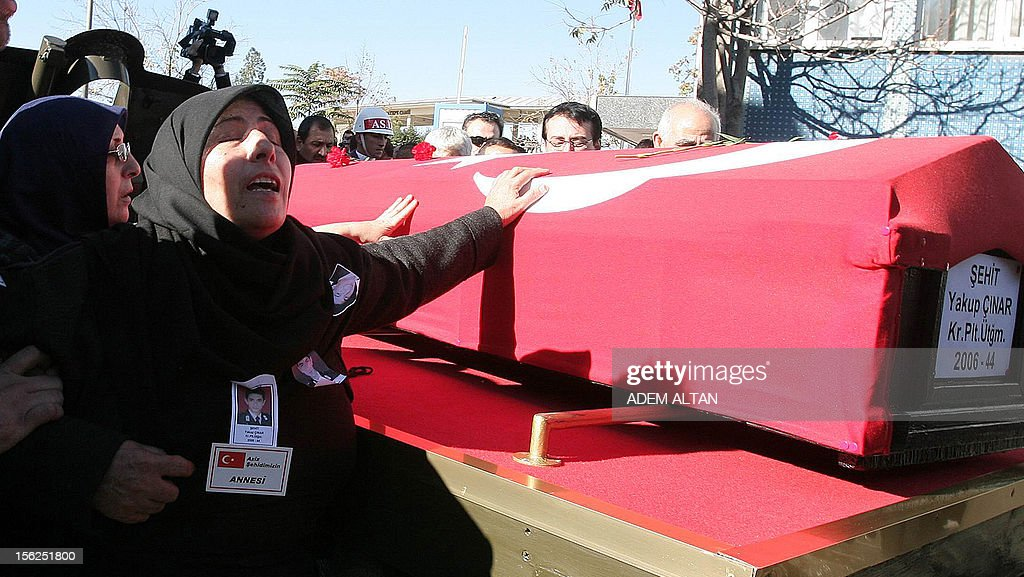 The mother of army officer Yakup Cinar, one of 17 Turkish soldiers who were killed in a helicopter crash early on November 9, 2012 in Siirt province, caresses his coffin during his funeral in Ankara on November 12, 2012. The Turkish military helicopter crashed on November 9, 2012 in bad weather in the southeastern city of Siirt, killing all 17 troops on board, local officials said. AFP PHOTO/ADEM ALTAN