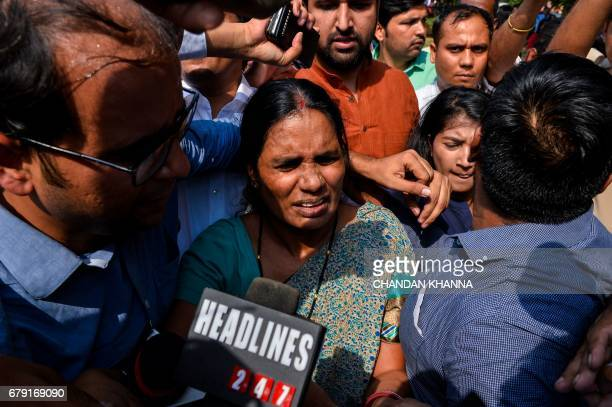 The mother of Indian gangrape victim 'Nirbhaya' walks through a crowd of media representatives as she leaves The Supreme Court in New Delhi on May 5...