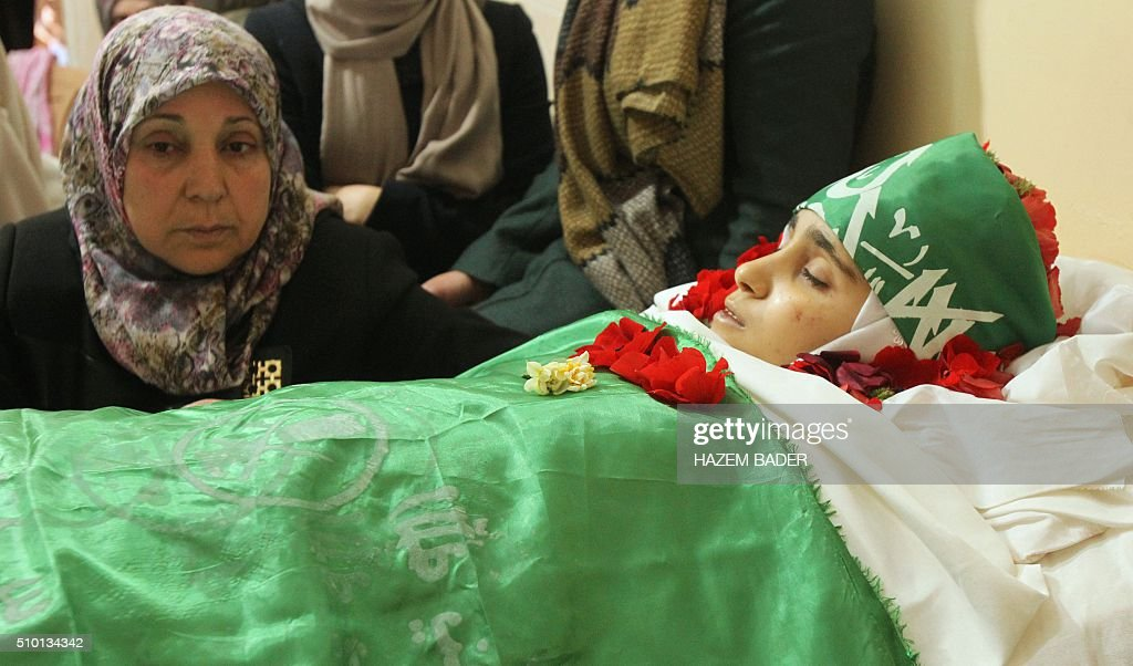 The mother of Palestinian Kalzar al-Uweiwi, a Palestinian teenager who was killed a day earlier following a reported stabbing attack, mourn over her body ahead of her funeral, in the Israeli occupied West Bank city of Hebron, February 14, 2016. Israeli forces shot dead Kalzar al-Uweiwi, 17, as she tried to stab a soldier in the city of Hebron on February 13, according to Israeli and Palestinian authorities. BADER