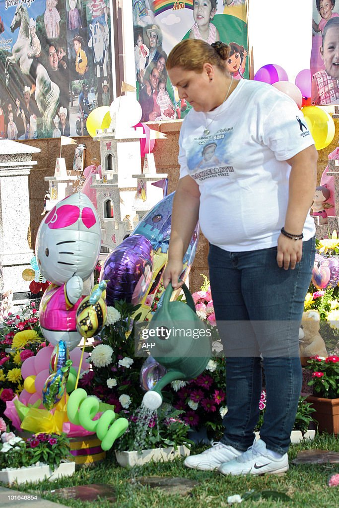 The mother of Monserrat Granados, one of the victims of a fire at a day care center, waters flowers in a square in Hermosillo, Sonora State, Mexico on June 5, 2010. Relatives of 49 children killed in a fire at a day care center a year ago demanded that officials - who failed to ensure the center's safety - be brought to justice. AFP PHOTO/Joel Garcia