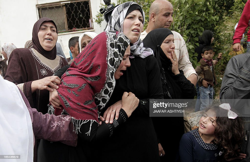 The mother (2nd-L) of Naji Balbisi, a 19-year-old Palestinian shot by Israeli troops, mourns with other relatives during his funeral in the West Bank town of Anabta near Tulkarem on April 4, 2013. The West Bank simmered with anger as thousands joined the funeral of prisoner Maisara Abu Hamdiyeh who died in an Israeli jail and similar numbers gathered to bury two teens shot dead overnight during clashes over the death of the prisoner, Israeli and Palestinian sources said.