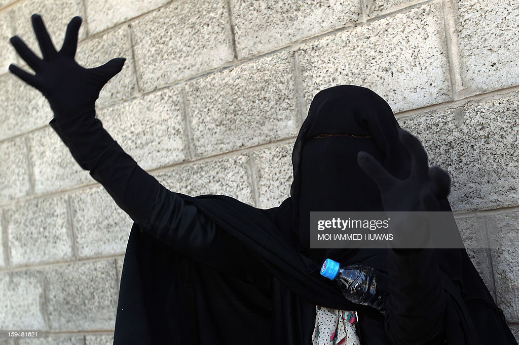 The mother of one of the nine Yemenis allegedly accused of complicity in a suicide bombing that had killed 86 soldiers, gestures as she waits outside of the state security court where the trial is taking place, on January 14, 2013 in Sanaa. The nine defendants who belong to an Al-Qaeda terrorist cell called Sawane, have notably been accused of 'participation in armed gang, conspiracy to assassinate officials.'