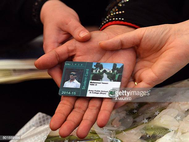 The mother of Pakistani student Muhammad Yaseen who was killed in the school massacre displays his school card during a ceremony to mark the first...