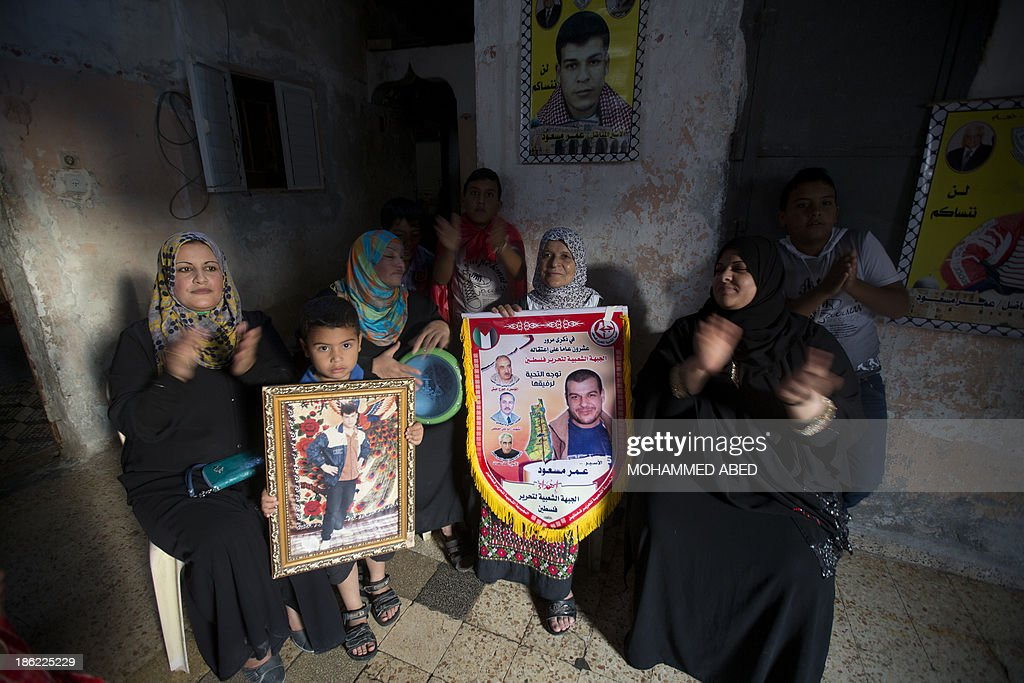 The mother (C) of Palestinian prisoner Omar Massud, held by Israel since 1993, holds a portrait of her son at their family house in Caza City on October 29, 2013, prior to his release. Israel is preparing to release 26 long-serving Palestinian prisoners, the second batch of 104 inmates who are to be freed in line with commitments to US-brokered peace talks.