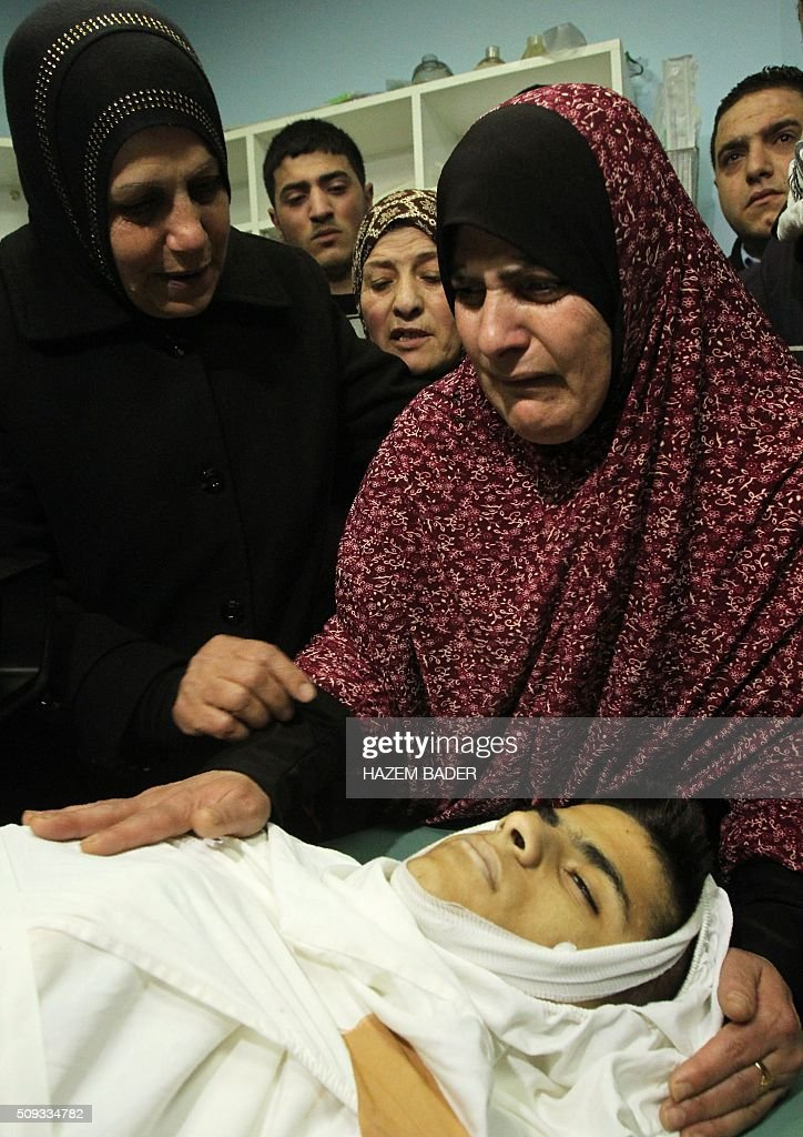 The mother of Palestinian youth Omar Maddi, 16, mourns over his body in the al-Mizan hospital in the West Bank city of Hebron on February 10, 2016 after he was killed during clashes with Israeli security forces in the area of the Al-Arroub refugee camp. A wave of violence that erupted in October has claimed the lives of 166 Palestinians, 26 Israelis, a US national, an Eritrean and a Sudanese. BADER