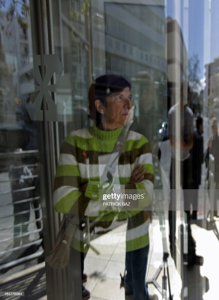 The mother of Philippos Philippou, an unemployed electrician, stands in the doorway of a Laiki (Popular) Bank in the Cypriot capital, Nicosia, on March 28, 2013, as her son visits the bank while people queue up outside following an unprecedented 12-day lockdown. Prior to entering the bank Phillippou said 'It will be a very bad day -- there will be swearing and a lot of anger,' but when he emerged from the bank along with his mother, he flashed a smile and said: 'There is confidence, everything was fine.' AFP PHOTO / PATRICK BAZ