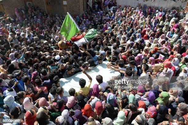 TOPSHOT The mother of slain militant Nasarullah Mir mourns over his body as they are carried during his funeral at Hajin village in Bandipora...