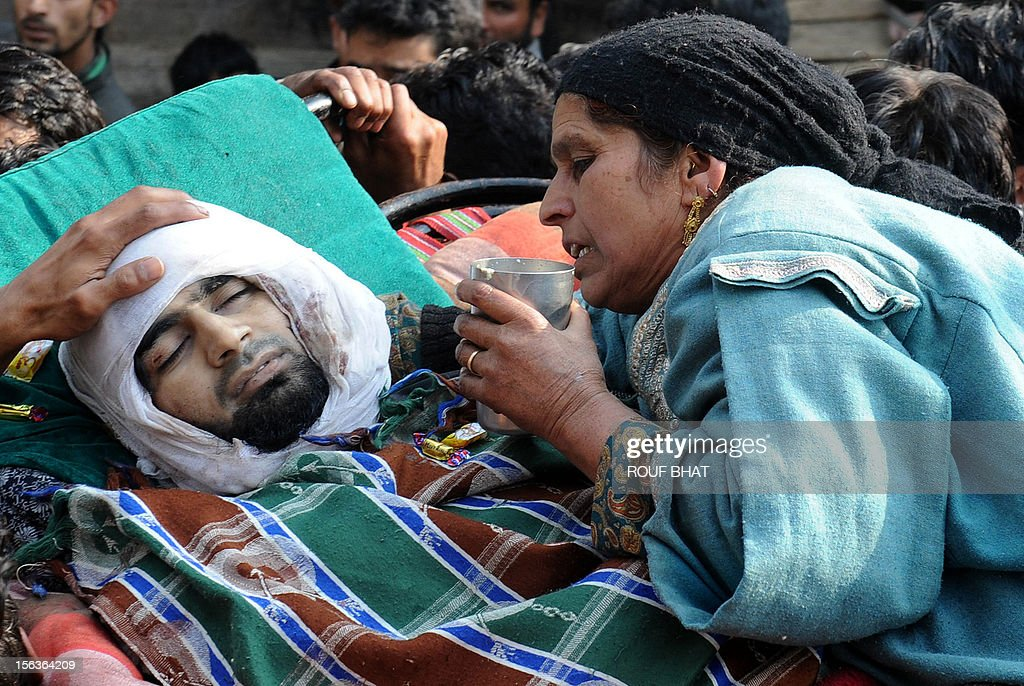 The mother (R) of suspected militant of Lashkar-e-Taiba, Shabir Ahmad mourns alongside his body carried by Kashmiri villagers during his funeral procession in Chingam, some 61 kms south of Srinagar on November 14, 2012. Thousands of Muslim villagers attended the funeral of Ahmad, a suspected rebel who was killed in a gunbattle with Indian troops in the restive Kashmir. AFP PHOTO/Rouf BHAT