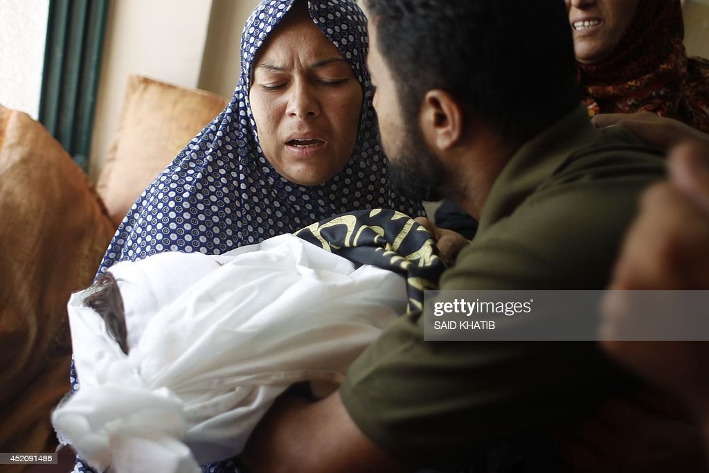 The mother (L) of three-year-old Palestinian child, Mouid al-Araj, carries her sons body during his funeral in Khan Yunis, in the southern Gaza Strip on July 13, 2014. Israeli strikes on Gaza killed a teenager and a woman, medics said, raising the overall death toll to 166 as the punishing air campaign entered its sixth day.