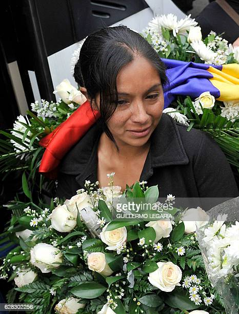 The mother of Yuliana a sevenyearold girl who was raped tortured and murdered holds white flowers and a Colombian flag after a mass held in the...