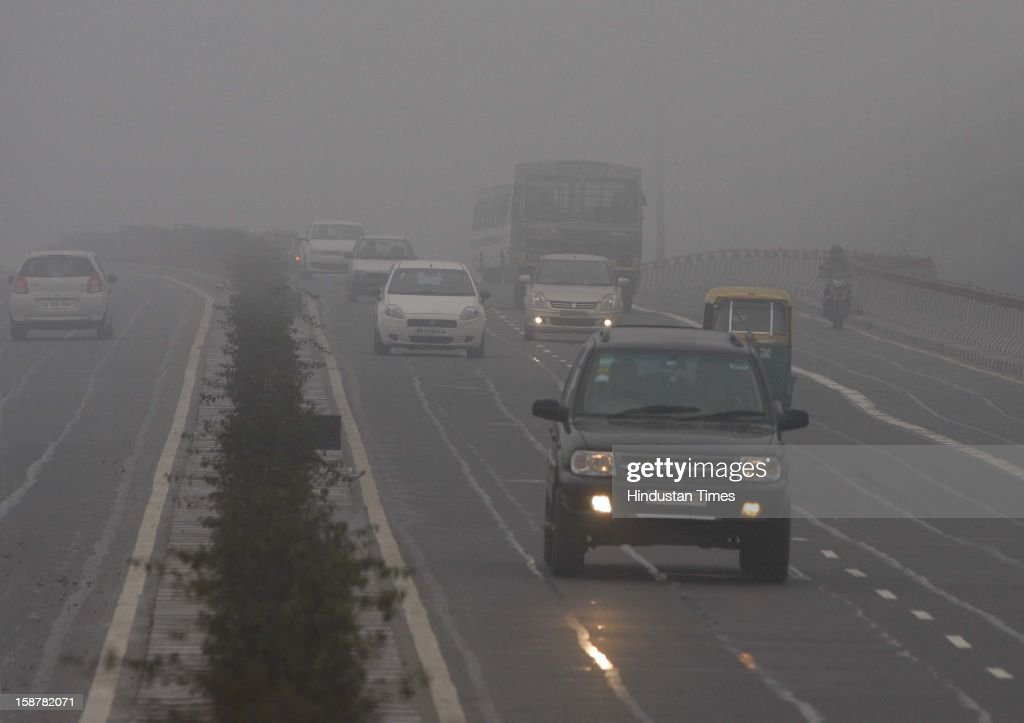 The motorists use lights while going to their destination in the cold and foggy weather near Akshardham, on December 28, 2012 in New Delhi, India. While the maximum temperature was recorded at 19 deg C, up from yesterday's temperature by 2.4 degrees, the minimum temperature today dipped to 6.3 deg C, a degree below the normal.