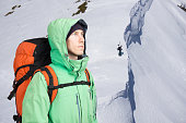 The mountaineer with backpack looks at the peak, standing against a winter mountain landscape.