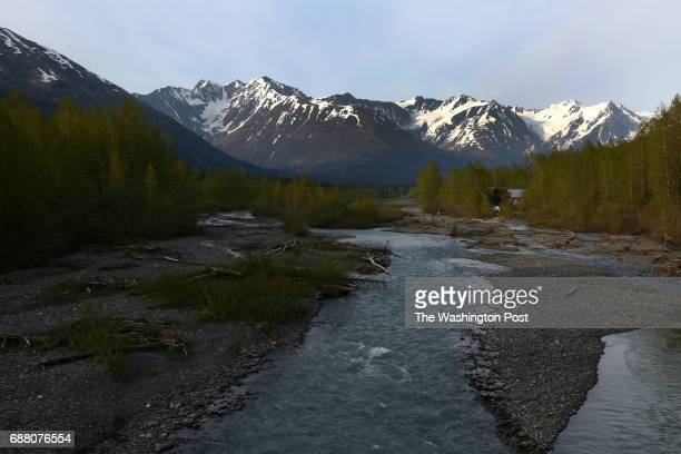 GIRDWOOD AK MAY The mountains sit behind a stream in Girdwood Alaska just outside Anchorage on May 15 2014 Tourists travel to this area some of whom...