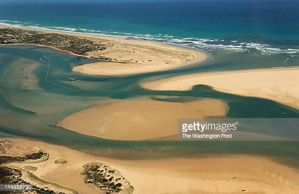 The mouth of Murray river as it meets the sea A floating crane attempts to dig out sand to get seawater flowing into the river's mouth to save...