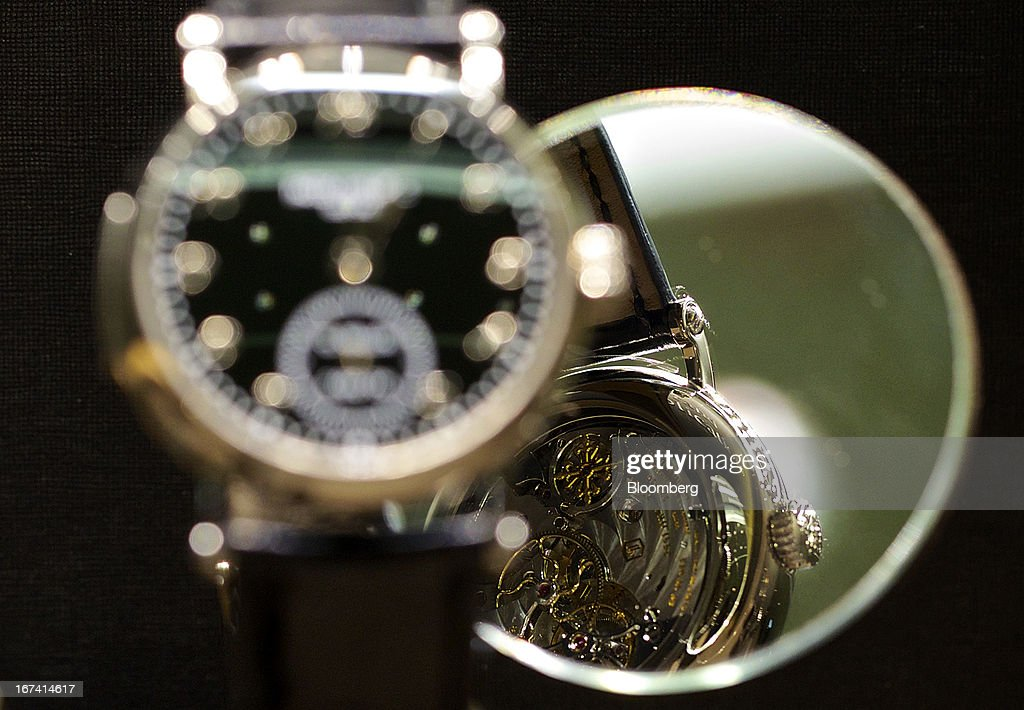 The movement of a 5539G-001 wristwatch in white gold, manufactured by Patek Philippe SA, is reflected in a mirror as the watch sits on display during the Baselworld watch fair in Basel, Switzerland, on Wednesday, April 24, 2013. The annual fair attracts 2,000 companies from the watch, jewelry and gem industries to show their new wares to more than 100,000 visitors. Photographer: Gianluca Colla/Bloomberg via Getty Images