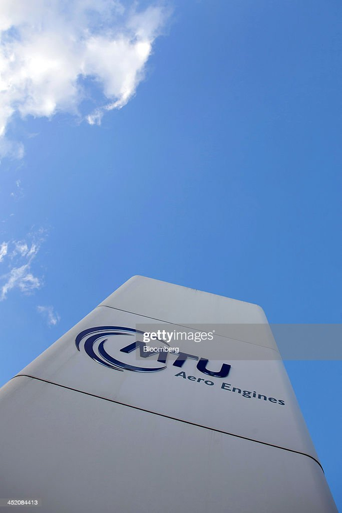 The MTU Aero Engines logo sits on a sign outside the company's headquarters in Munich, Germany, on Monday, Nov. 25, 2013. MTU Aero Engines Holding AG said it will eliminate jobs and cut costs to boost profitability as the German manufacturer predicted strong growth in sales of new engines next year. Photographer: Krisztian Bocsi/Bloomberg via Getty Images