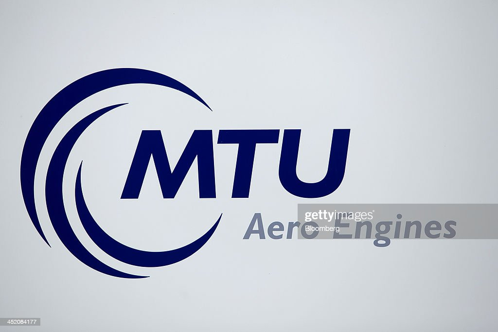 The MTU Aero Engines logo sits on display at the company's headquarters in Munich, Germany, on Monday, Nov. 25, 2013. MTU Aero Engines Holding AG said it will eliminate jobs and cut costs to boost profitability as the German manufacturer predicted strong growth in sales of new engines next year. Photographer: Krisztian Bocsi/Bloomberg via Getty Images