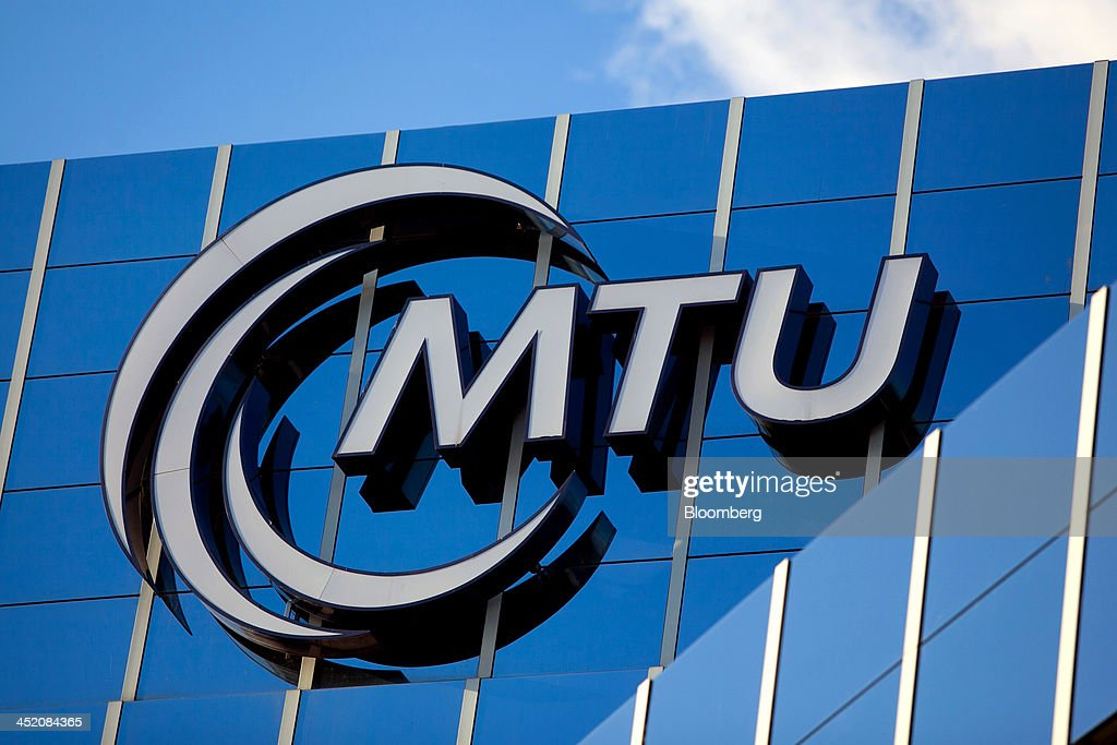 The MTU Aero Engines logo sits on the exterior of the company's headquarters in Munich, Germany, on Monday, Nov. 25, 2013. MTU Aero Engines Holding AG said it will eliminate jobs and cut costs to boost profitability as the German manufacturer predicted strong growth in sales of new engines next year. Photographer: Krisztian Bocsi/Bloomberg via Getty Images