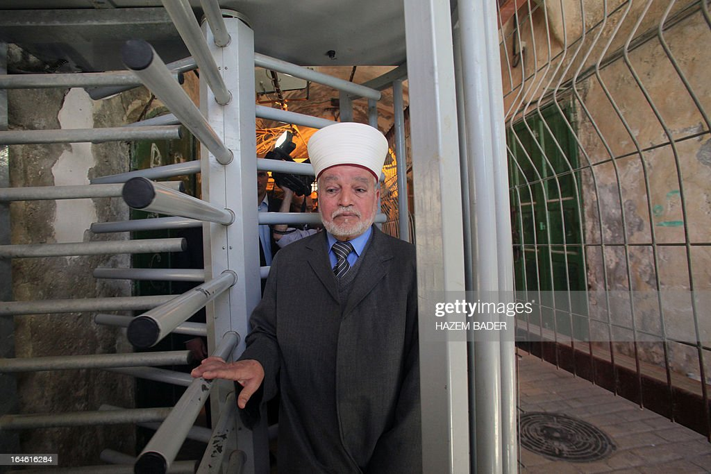 The Mufti of Jerusalem and Palestine, Sheikh Mohammed Hussein passes through an iron gate as he crosses an Israeli checkpoint in the occupied West Bank city of Hebron to go to the Ibrahimi Mosque or the Tomb of the Patriarch on March 25, 2013. The Ibrahimi Mosque and the Tomb of the Patriarch will be closed to Muslims on March 27 and 28 due to the Jewish holiday of Pesach (Passover). AFP PHOTO/HAZEM BADER