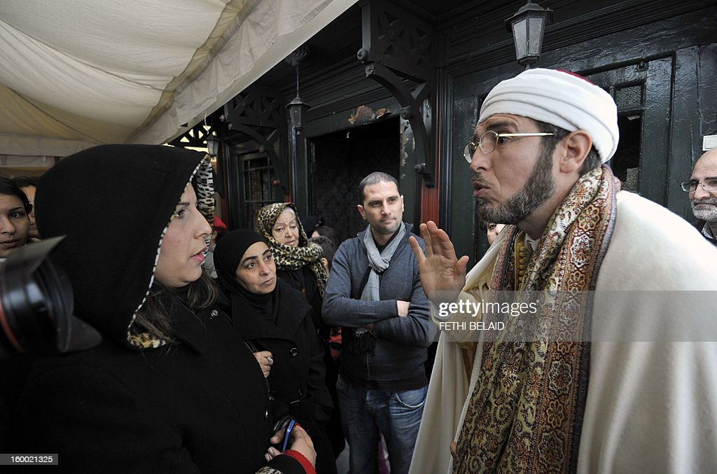 The Mufti of Sidi Bou Said speaks with visitors of the mausoleum in Tunisia on January 24, 2013. The renovation project of the recently torched mausoleum is mid-way through, as it was prepared for a modest reopening to welcome visitors commemorating the birth of Prophet Mohammed, known in Arabic as 'al-Mawlid al-Nabawi'. In the 35th such attack in seven months, unidentified assailants hurled Molotov cocktails at the Sidi Ahmed Uwerfelli shrine in Akuda, 140 kilometres (85 miles) south of Tunis.