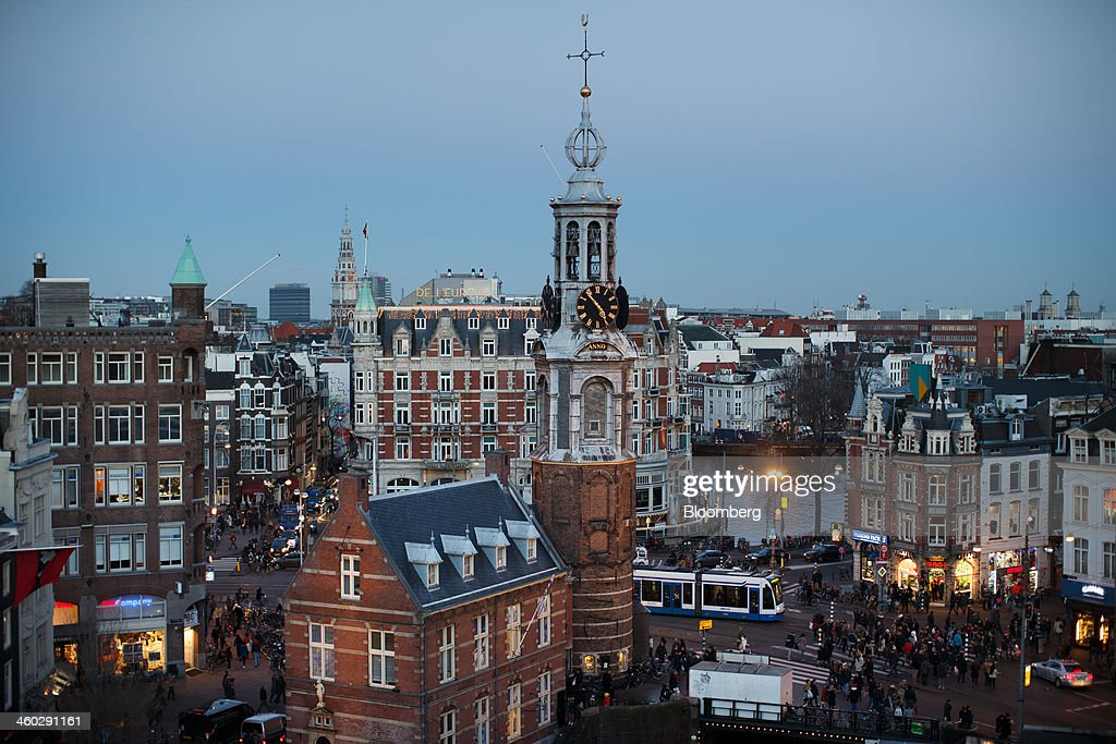 The Munttirren tower stands as shoppers cross a road and pass retail stores in this skyline view of Amsterdam, Netherlands, on Thursday, Jan. 2, 2014. The Netherlands will grow by 0.5 percent in 2014 as the world economy improves and consumer confidence picks up, the country's central bank forecast Dec. 9. Photographer: Jasper Juinen/Bloomberg via Getty Images
