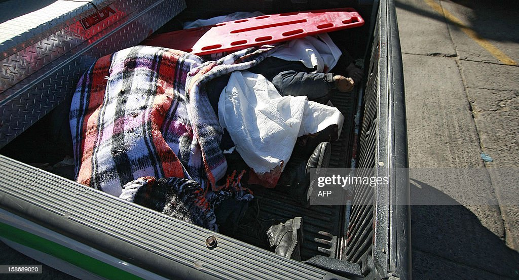 The murdered bodies of three municipal police officers and one civilian are transferred in a medical forensic pickup truck in Degollado, Jalisco State, Mexico on December 23, 2012. Clashes took place between criminal organizations and the police of four different municipalities, leaving 13 people dead. AFP PHOTO/STR