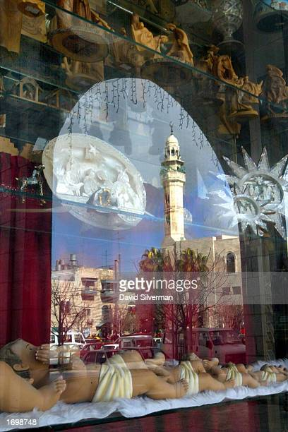 The Muslim mosque that dominates Manger Square is reflected amongst the displays of baby Jesus dolls and other Christian icons in the window of a...