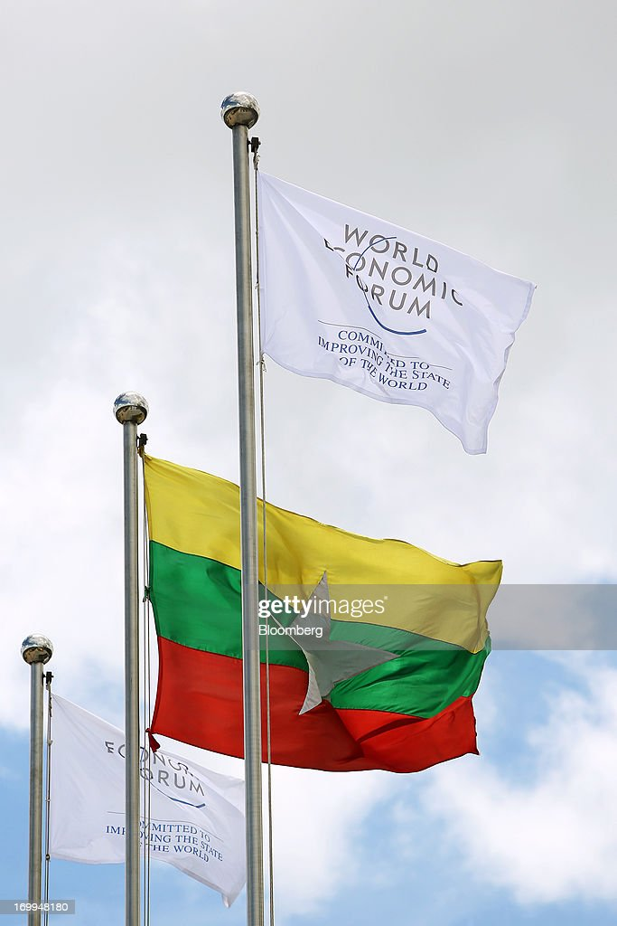 The Myanmar flag flies alongside flags of the World Economic Forum (WEF) at the entrance to the Myanmar International Convention Center ahead of the World Economic Forum on East Asia in Naypyidaw, Myanmar, on Wednesday, June 5, 2013. Myanmar hosts the three-day World Economic Forum on East Asia starting today, with heads of state and executives from companies including General Electric Co., Coca-Cola Co. and WPP Plc attending. Photographer: Dario Pignatelli/Bloomberg via Getty Images