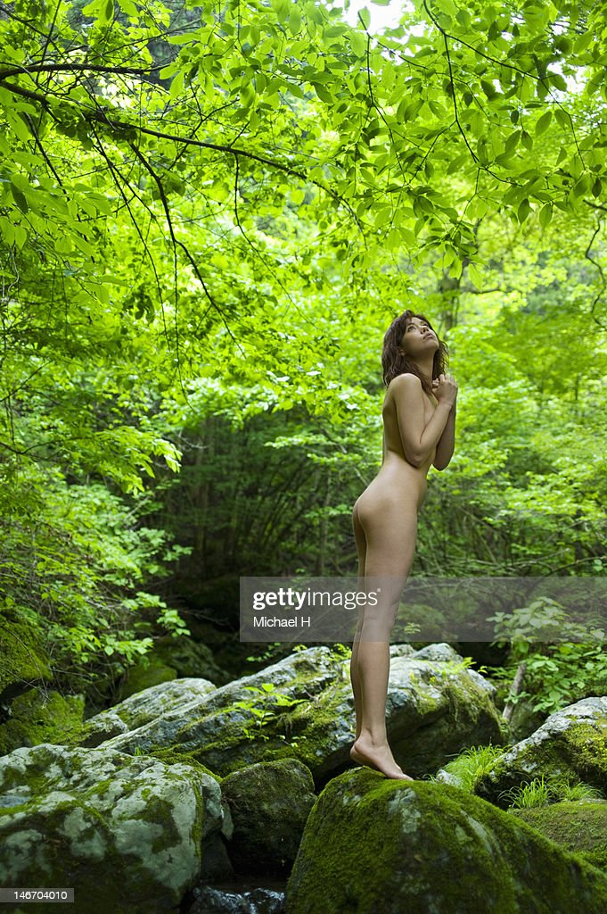 The naked woman who looks up at trees : Stock Photo