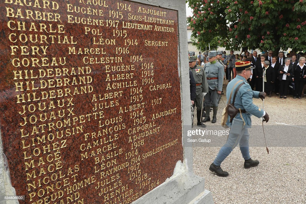 The names of local French soldiers killed in World War I are inscribed on a war memorial as local visitors as well as history reenactors dressed as World War I Austro-Hungarian soldiers attend a commemoration ceremony in Haudainville village on May 28, 2016 near Verdun, France. The governments of France and Germany will commemorate the 100th anniversary of the World War I Battle of Verdun with ceremonies tomorrow. Approximately 300,000 soldiers lost their lives in the 10-month campaign that was among the most grueling battles of World War I.