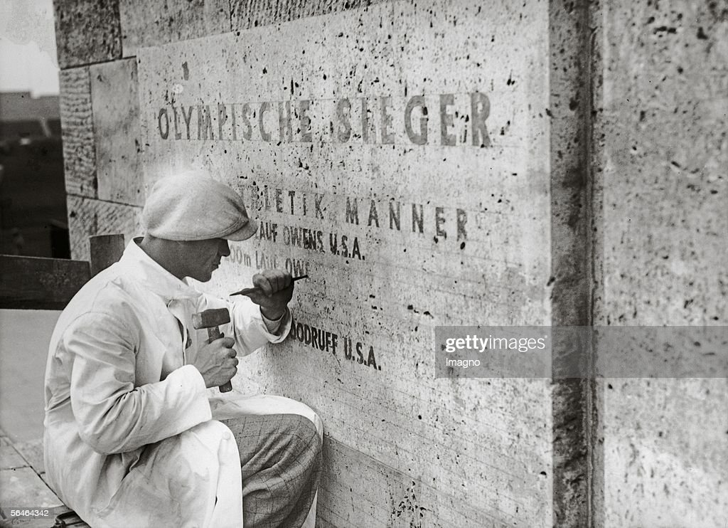 The names of the winners of the 11th Olympic Games are being chiseled into the 'Honor Board' of the marathon gate. Photography. Berlin. Germany. 1936. (Photo by Imagno/Getty Images) [Die Namen der Sieger der XI. Olympischen Spiele werden in die Ehrentafeln des Marathontors gemeisselt. Photographie. Berlin. Deutschland. 1936.]