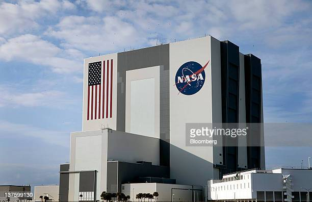The NASA logo and US flag are seen on the outside of the Vehicle Assembly Building at the NASA Kennedy Space Center in Cape Canaveral Florida US on...