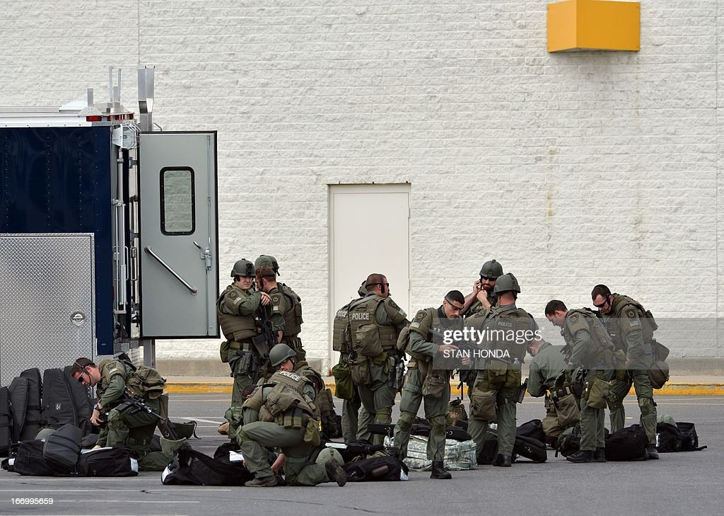 The Nashua (New Hampshire) Police Department SWAT team prepares in the Watertown Mall as a search for the second of two suspects wanted in the Boston Marathon bombings takes place April 19, 2013 in Watertown, Massachusetts. Thousands of heavily armed police staged an intense manhunt Friday for a Chechen teenager suspected in the Boston marathon bombings with his brother, who was killed in a shootout. Dzhokhar Tsarnaev, 19, defied the massive force after his 26-year-old brother Tamerlan was shot and suffered critical injuries from explosives believed to have been strapped to his body. AFP PHOTO/Stan HONDA