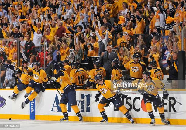 The Nashville Predators bench and fans erupt in celebration as the horn sounds in a 21 series clinching win against the Detroit Red Wings in Game...