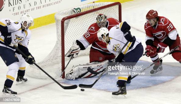 The Nashville Predators' Chris Mueller gets ready to put the puck past Carolina Hurricanes goalie Justin Peters and defenseman Justin Faulk for the...