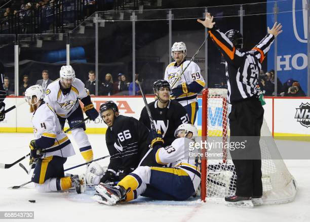 The Nashville Predators defend against Joshua HoSang and Anders Lee of the New York Islanders during the second period at the Barclays Center on...