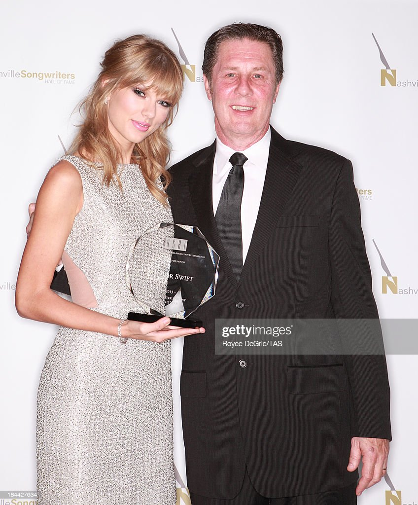 The Nashville Songwriters Association International named seven-time GRAMMY winner <a gi-track='captionPersonalityLinkClicked' href=/galleries/search?phrase=Taylor+Swift&family=editorial&specificpeople=619504 ng-click='$event.stopPropagation()'>Taylor Swift</a> their 2013 Songwriter/Artist of the Year. Swift's 6th time to win the award, she has now won this award more times than any other songwriter/artist, surpassing 5-time winners Vince Gill and Alan Jackson. She remains the youngest artist ever to earn the award. Her album RED reached #1 in 50 countries, and has sold more than 6 million copies. Yesterday, Swift opened the $4 million <a gi-track='captionPersonalityLinkClicked' href=/galleries/search?phrase=Taylor+Swift&family=editorial&specificpeople=619504 ng-click='$event.stopPropagation()'>Taylor Swift</a> Education Center at the Country Music Hall of Fame and Museum. Taylor is joined by NSAI Executive Director Bart Herbison. at on October 13, 2013 in Nashville, Tennessee.