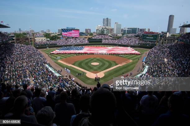 The national anthem is performed with an American flag in center field prior to a game between the Tampa Bay Rays and the Chicago Cubs on July 4 at...